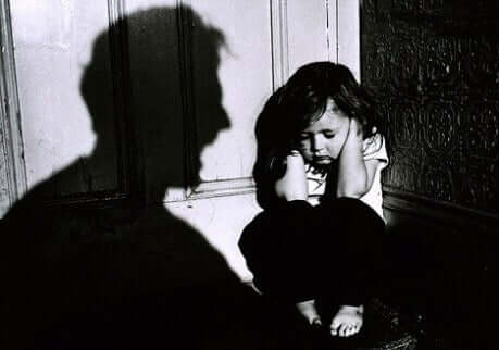 abused little girl covering hear ears so not to hear someone screaming at her- can cause obesity in her adult life