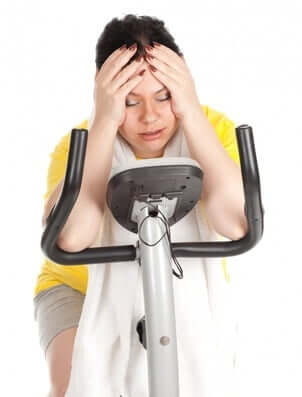 best exercise- woman on stationery bike has over-exercised and created stress