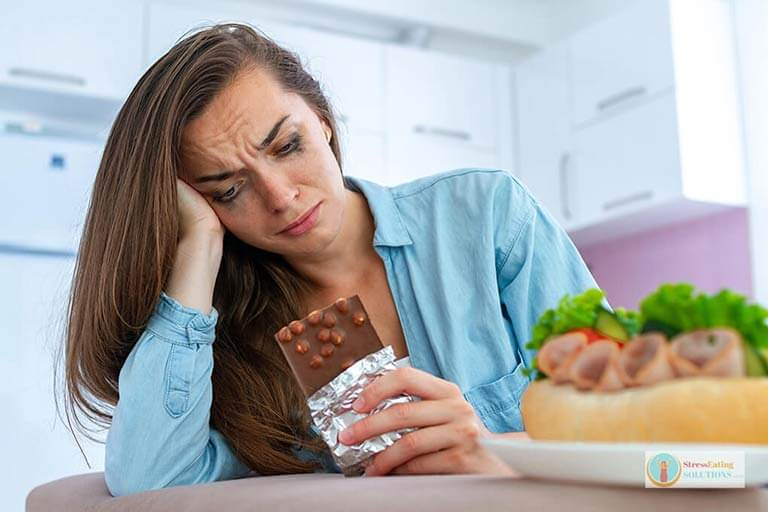 Sad, unhappy woman stress eating chocolate and sweets