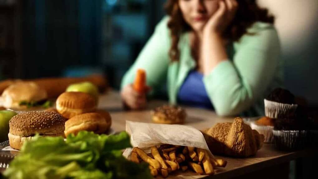 a woman looks longingly at food she wants to eat while holding a carrot. This is the cause of compulsive binge eating.