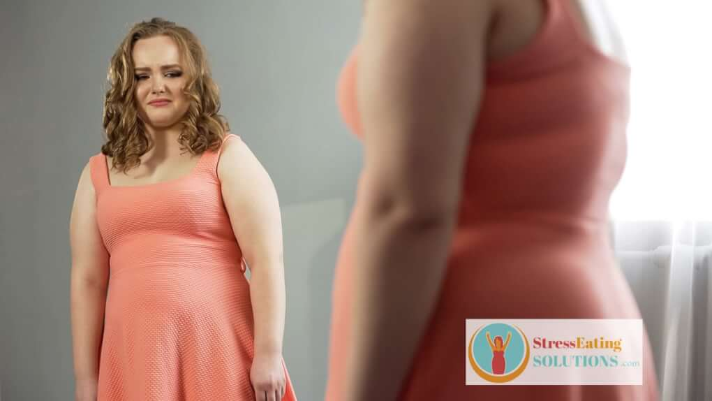 sad heavy woman looking at her reflection in the mirror -thinks she needs to lose weight due to poor body image